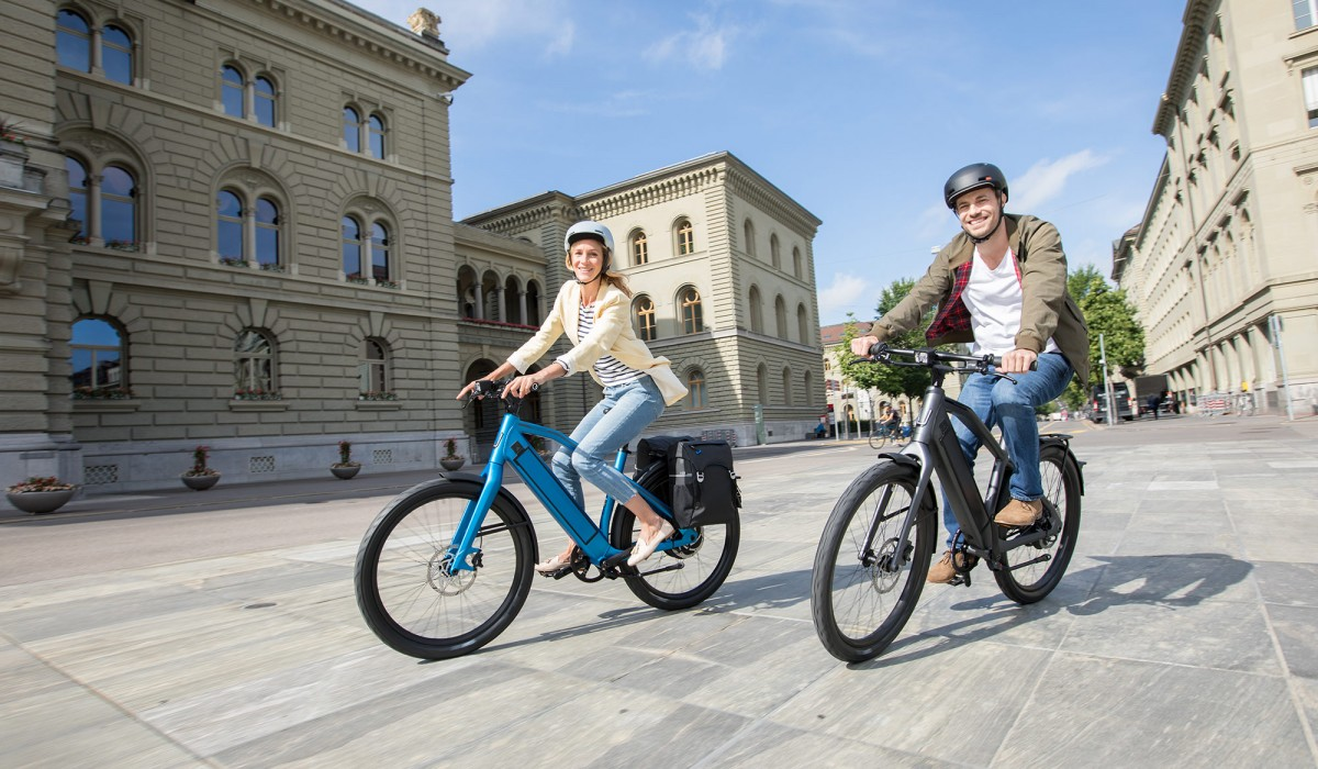 Couple with Stromer ST2 e-bikes in Royal Blue and Dark Grey riding through the city.